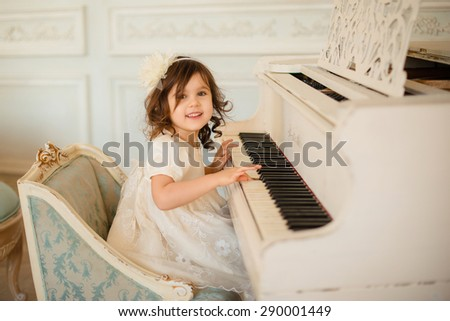 beautiful little girl playing piano in light room - stock photo