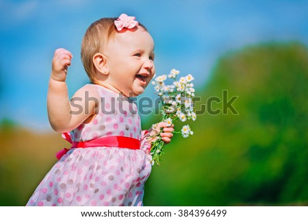Beautiful little girl playing with flowers on green grass in nice sunny weather - stock photo