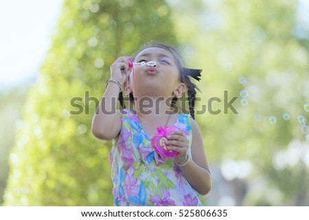 Beautiful little girl playing with soap bubbles nature,  Portrait of a child in warm colors at sunset