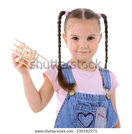 Beautiful little girl plays with wooden plane isolated on white background - stock photo