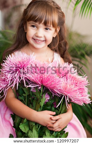 Beautiful little girl posing with a large bouquet of flowers in a luxurious  pink dress at