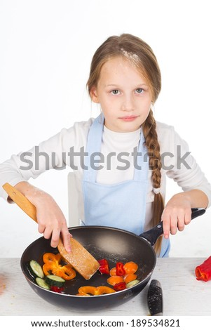 Beautiful little girl prepares vegetables in a frying pan isolated on white background