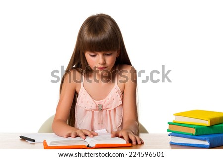 Beautiful little girl reading a book while sitting at table on white background - stock photo