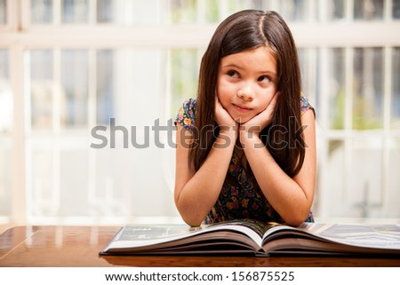 Beautiful little girl reading and daydreaming in the living room - stock photo