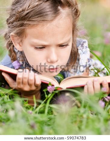 Beautiful little girl reads book, lying on green lawn. - stock photo