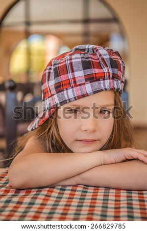 Beautiful little girl sitting at checkered table and think.