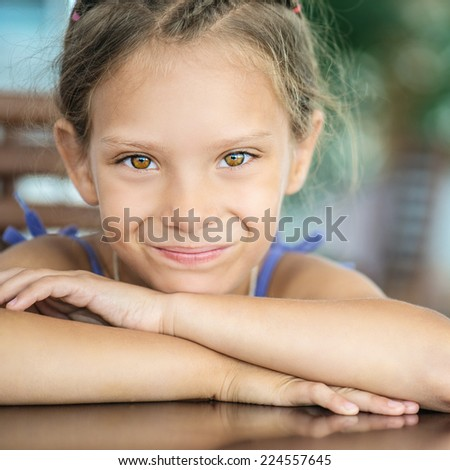 Beautiful little girl sitting at table and smiling. - stock photo