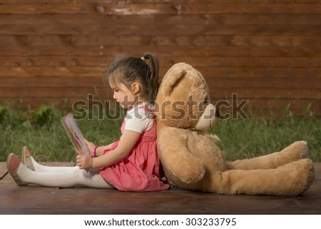 Beautiful little girl sitting back with toy bear outside in backyard playground, reading to her little plush friend - stock photo