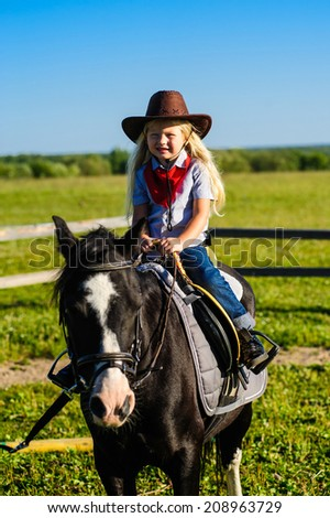 beautiful little girl sitting cowboy riding in the saddle on a horse a horse on a background of green meadows and blue sky - stock photo