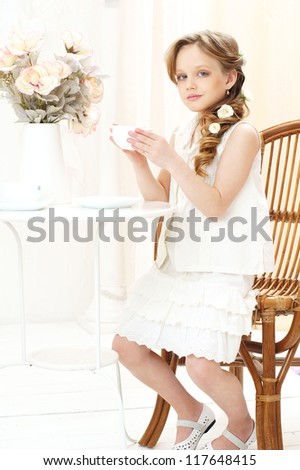 beautiful little girl sitting in cafe and drinking tea
