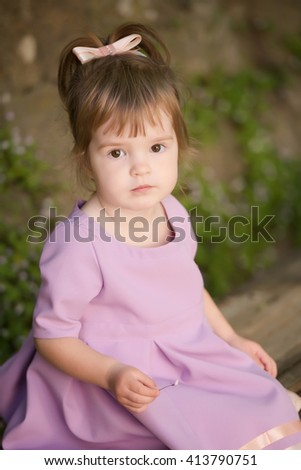 beautiful little girl sitting on a bench against the wall curled with ivy - stock photo