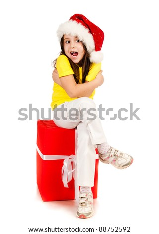 beautiful little girl sitting on red gift in santa hat