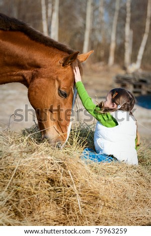 Beautiful little girl sitting on the hay, which eats the horse and flatter it. True Friendship. - stock photo