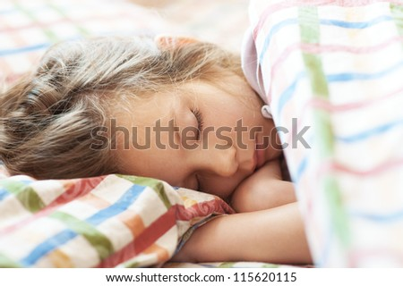 Beautiful little girl sleeping in bed close-up. - stock photo