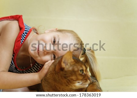 Beautiful little girl smiling and hugging cat. - stock photo