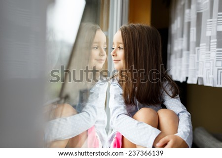 Beautiful little girl smiling and watching out the window. A child looks out the window. Young girl looking from window. Portrait of cheerful kid sits at windowsill. - stock photo