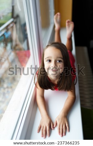 Beautiful little girl smiling and watching out the window. A child looks out the window. Young girl looking from window. Portrait of cheerful kid lies at windowsill. - stock photo