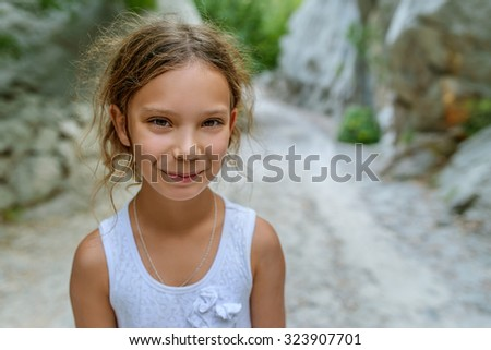 Beautiful little girl smiling on background of summer green park. - stock photo