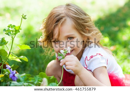 beautiful little girl sniffing flowers