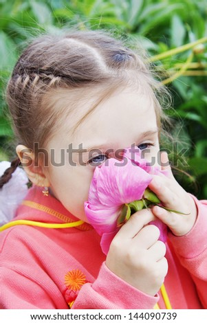 Beautiful Little Girl Sniffs Large Peony Flower - stock photo