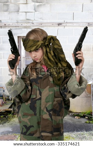 Beautiful little girl soldier with a couple of guns - stock photo