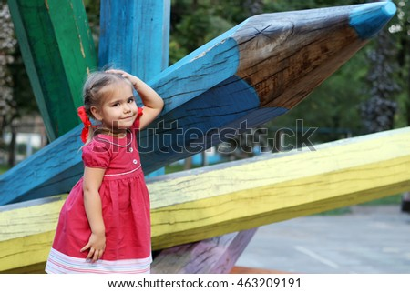 Beautiful little girl standing before the giant color wood pencil, ready back to school, fall outdoors, education concept