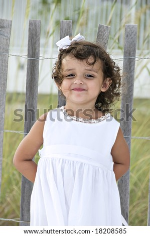 Beautiful little girl standing by a wooden fence on the beach with a silly look on her face. - stock photo
