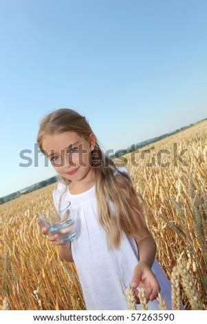 Beautiful little girl standing in wheat field - stock photo