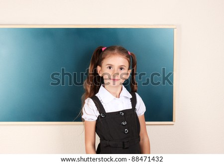 beautiful little girl standing near blackboard in the classroom - stock photo