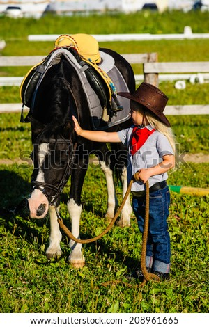 beautiful little girl stroking horse cowboy, on a background of green meadows and blue sky - stock photo
