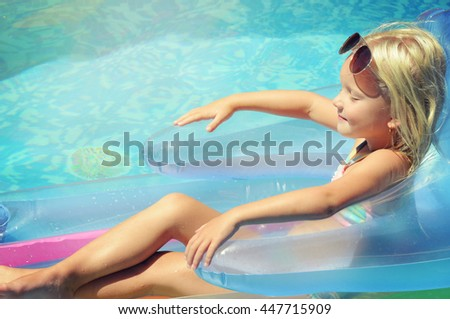 Beautiful little girl sunning at the pool - stock photo