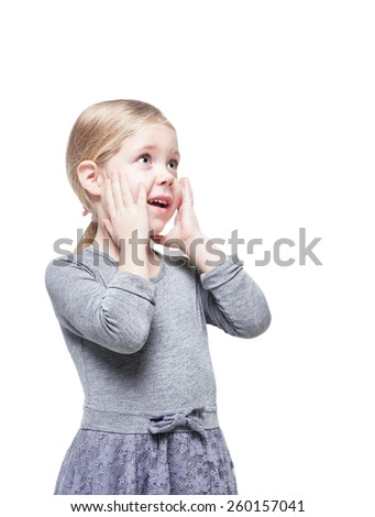 Beautiful little girl surprised looking up on something isolated over white background - stock photo