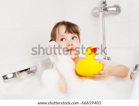 beautiful little girl taking a relaxing bath with foam and playing with a toy duck - stock photo
