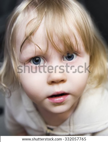 Beautiful little girl the blonde with huge blue eyes looking up in fear, wonder and amazement - stock photo