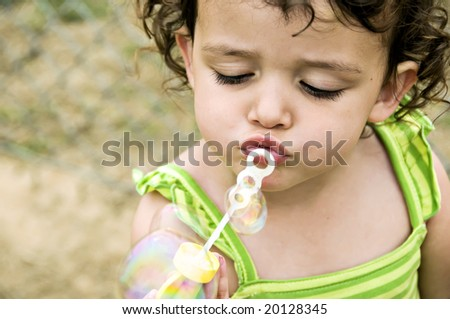 Beautiful little girl trying to blow bubbles. - stock photo
