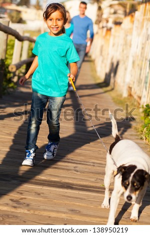 beautiful little girl walking her dog in the morning with parents - stock photo