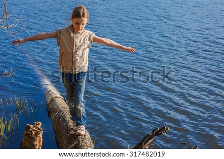 Beautiful little girl walking on trunk of tree that fell into lake. - stock photo