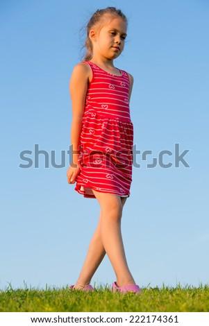 Beautiful little girl walks on green grass in summer park - stock photo