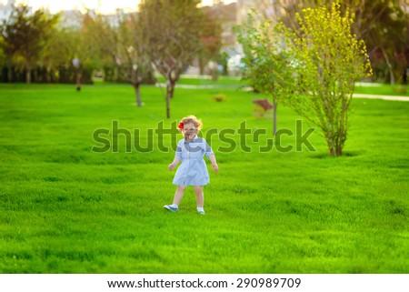 beautiful little girl walks on nature - stock photo