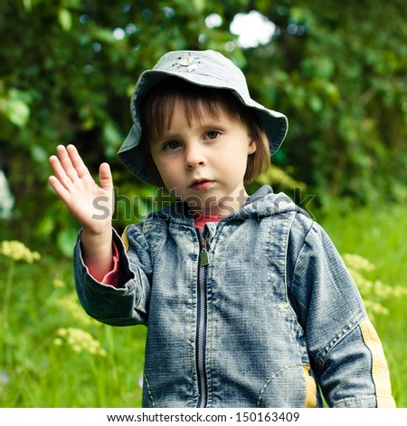 Beautiful little girl waves her hand on a background of green grass