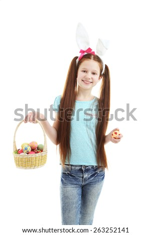 Beautiful little girl wearing Easter bunny ears and holding wicker basket with Easter eggs, isolated on white - stock photo