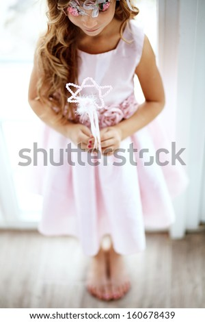 Beautiful little girl wearing fairy costume with magic wand shallow dof - stock photo
