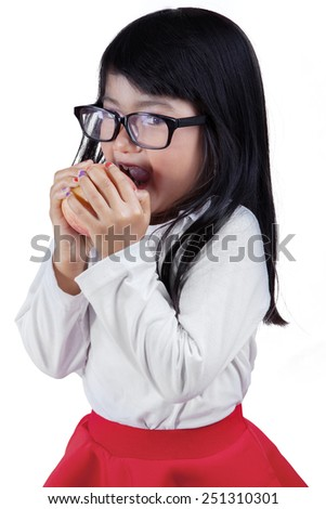 Beautiful little girl wearing glasses and eating a red apple in the studio, isolated on white background - stock photo