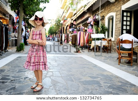 Beautiful little girl wearing pink dress, hat and sunglasses walking along the street - stock photo