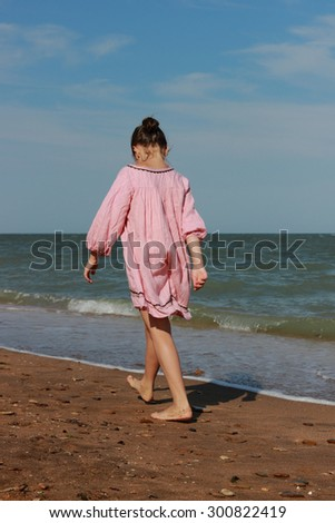 Beautiful little girl wearing summer dress playing and running over the seaside in Crimea