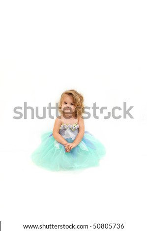 Beautiful little girl wears a ballerina costume and sits in an all white room.  She has blond curls falling around her face and is looking dreamy and angelic. - stock photo