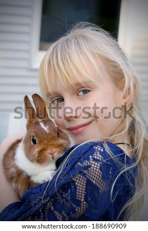 Beautiful little girl with a cute bunny - stock photo