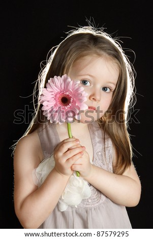 Beautiful little girl with a flower.