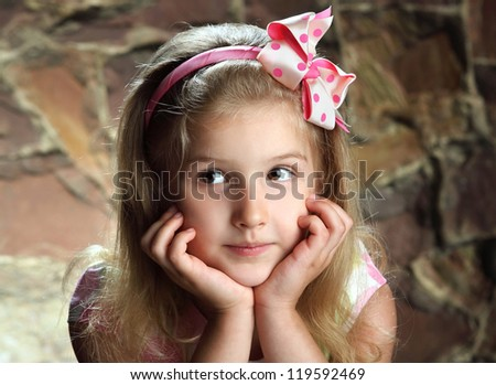 beautiful little girl with a pink bow on her head - stock photo