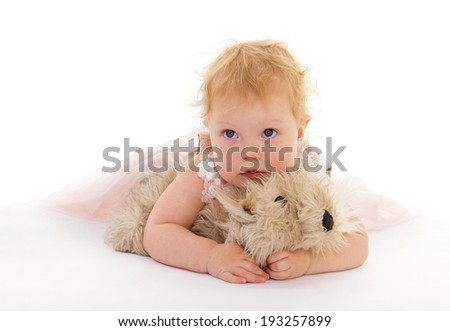 Beautiful little girl with a toy dog - stock photo